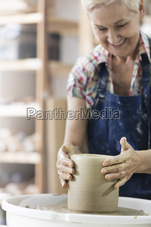 smiling senior woman using pottery wheel