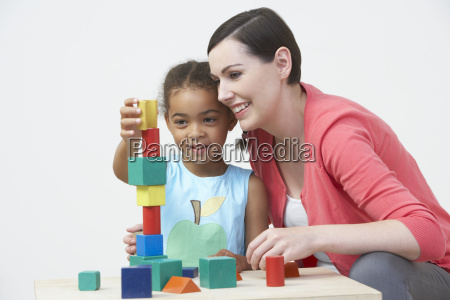 teacher and pre school pupil playing