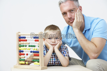 puzzled father and son looking abacus