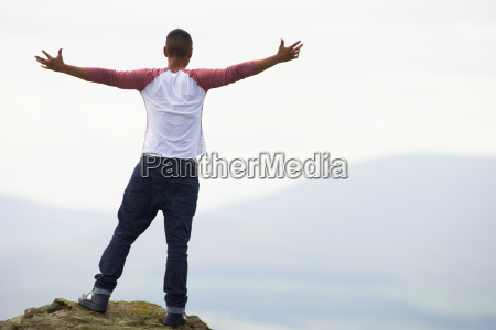 young man standing on rock with