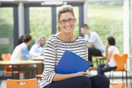 female, tutor, sitting, in, classroom, with - 19407670