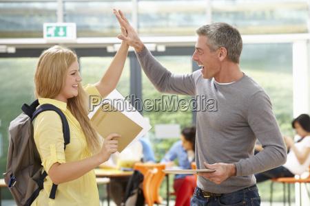 teacher, congratulating, pupil, on, successful, exam - 19407818