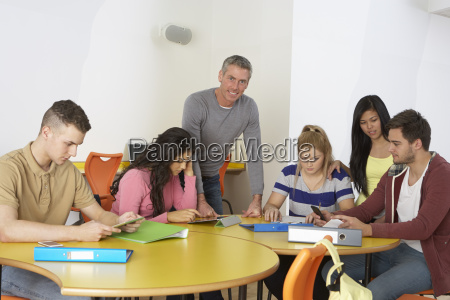 college students with tutor using digital