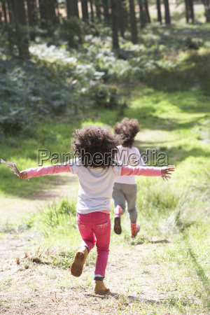two girls playing in woods together