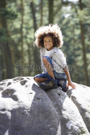 boy climbing on rock in countryside
