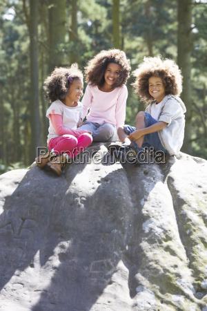 three children climbing on rock in