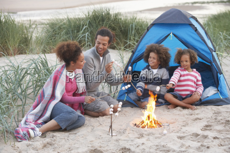 family camping on beach and toasting