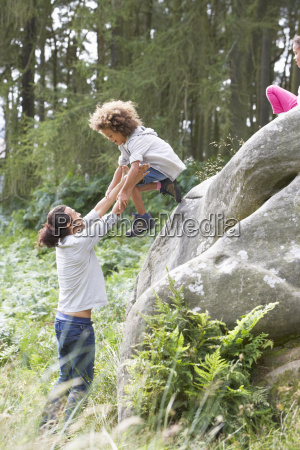 father, helping, children, to, jump, off - 19408904