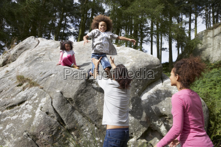 father, helping, children, to, jump, off - 19408960