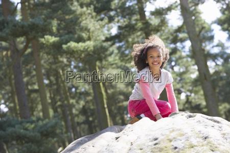 girl, climbing, on, rock, in, countryside - 19408858