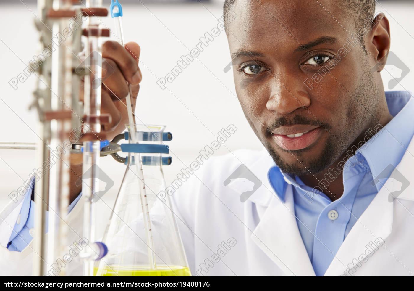 scientist, studying, liquid, in, flask - 19408176