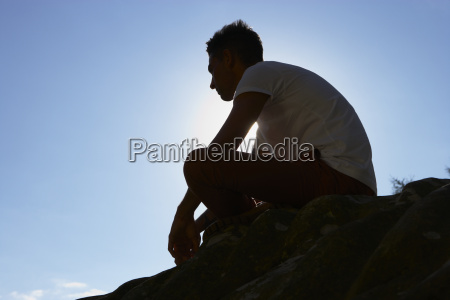 silhouette, of, young, man, sitting, on - 19408688