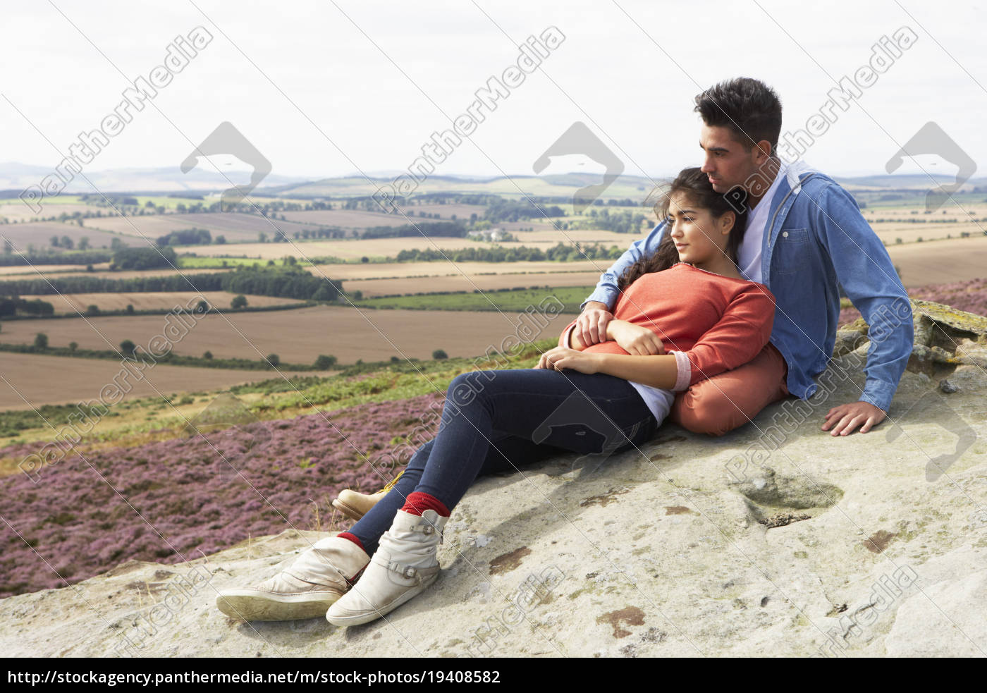 young, couple, sitting, on, rock, admiring - 19408582