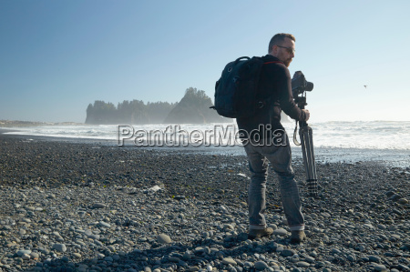 male photographer on beach carrying camera