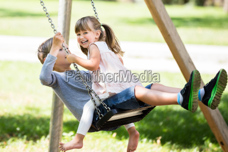 brother and sister enjoying on swing