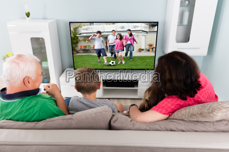 grandparent and grandchildren watching television together