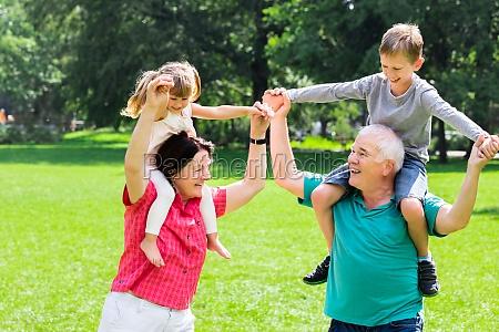 happy, grandparents, giving, grandchildren, piggyback, ride - 19412714