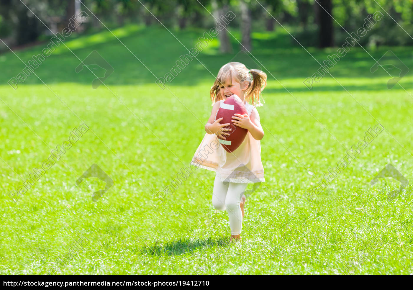 little, girl, playing, with, rugby, ball - 19412710