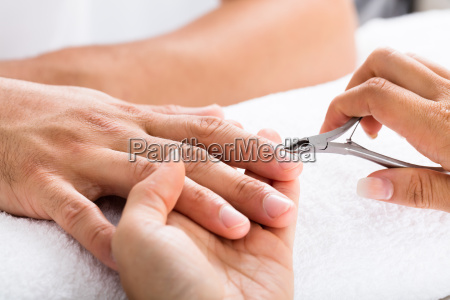 manicurist, cutting, off, the, cuticle, from - 19412530