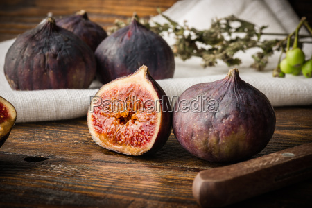 ripe purple figs on wooden table