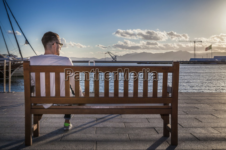 young man relaxing on bench by
