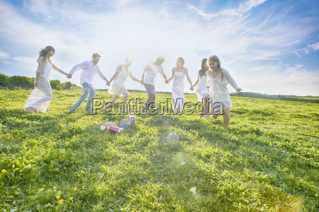 seven young adult friends holding hands