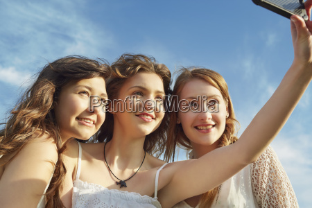 three young women smiling for selfie
