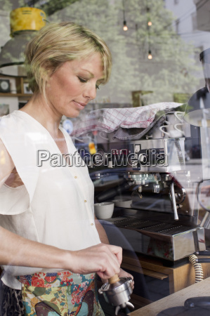 mid adult woman making coffee in