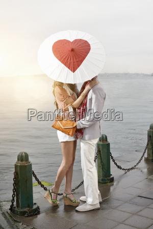 romantic young couple behind heart umbrella