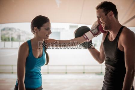 young woman wearing boxing glove touching