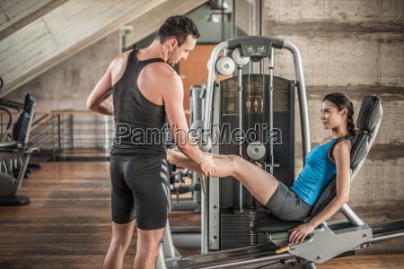 personal trainer mit frau mit gewichts