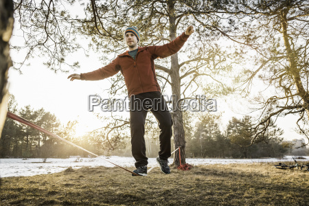 young man practicing on slackline in