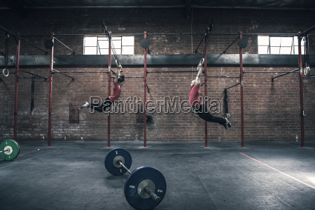 young male and female crossfitter swinging
