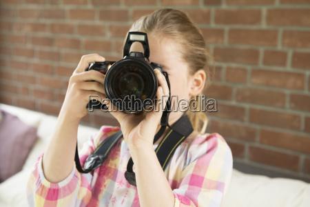 girl taking photograph towards camera