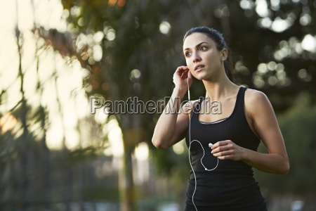 mid adult woman putting in earphones