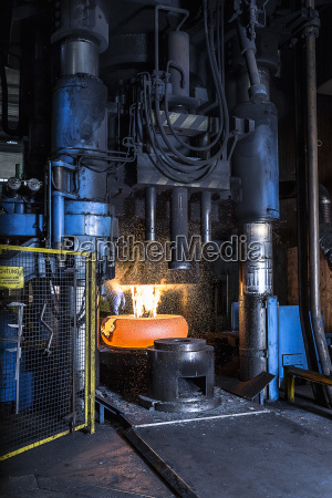 manufacturing machine shaping red hot steel