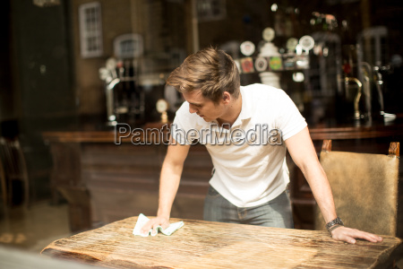 young man cleaning table in public