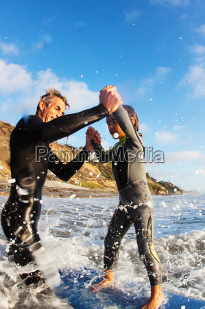 father and daughter jumping in sea
