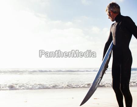 man at coast with surfboard encinitas
