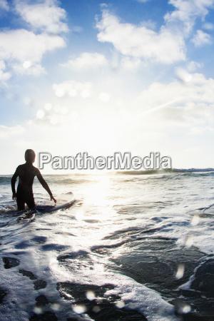 boy in sea with surfboard encinitas