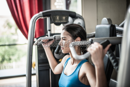 junge frau die gewichtsausruestung verwendet