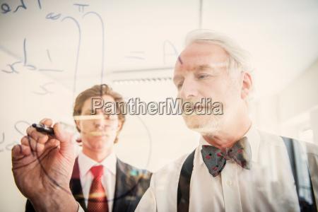 two men writing on transparent wipe