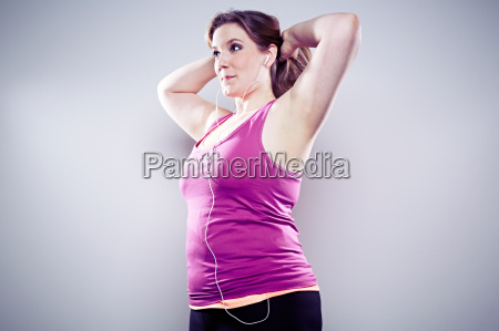 young woman wearing earphones arms up