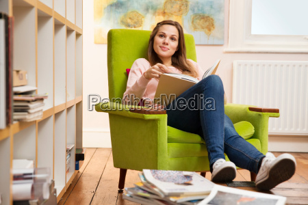 young woman sitting in green armchair