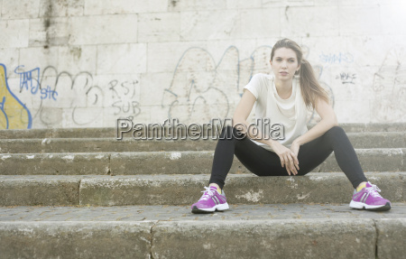sporty young woman sitting on steps