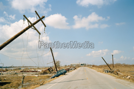 fallen telephone poles and crashed car