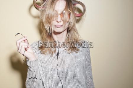 woman in hair rollers holding earphones