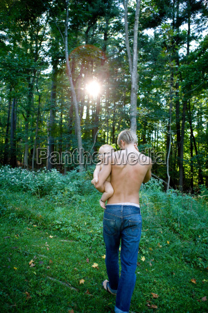 father carrying baby girl in forest