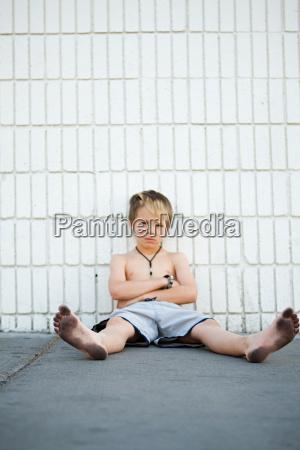 boy with dirty feet sitting by