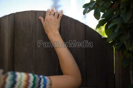 womans hand on gate
